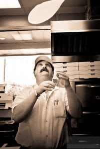 chef tossing dough at pizza palace